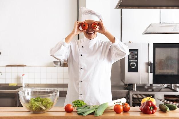 Foto di chef donna allegra che indossa un pasto di cucina bianco uniforme con verdure fresche, in cucina al ristorante