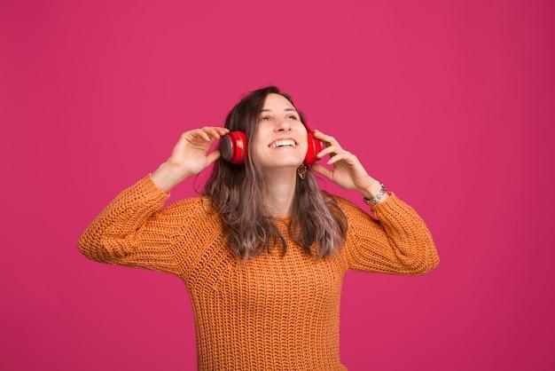 Foto di allegra giovane donna, godendo l'ascolto di musica in cuffia, in piedi sopra lo spazio rosa
