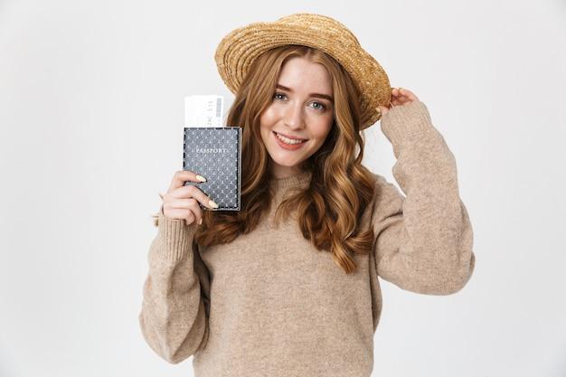 Foto di una giovane ragazza allegra e carina in posa isolata sul muro bianco che indossa un cappello che tiene il passaporto con i biglietti.