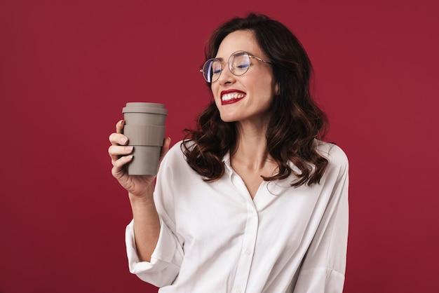 Foto di una giovane donna allegra e felice con gli occhiali che beve caffè isolato sul muro rosso.