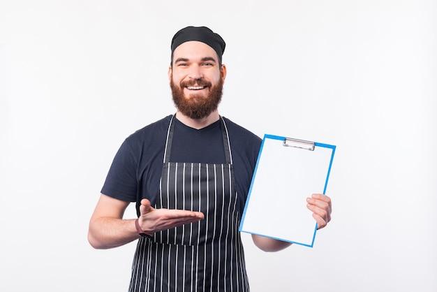 Foto dell'uomo del cuoco unico che mostra la lista di controllo per la preparazione
