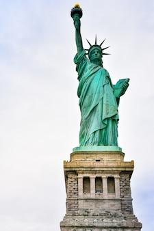 Primo piano della foto della statua della libertà in una giornata di sole e cielo blu con nuvole. isola della libertà. nyc, usa.