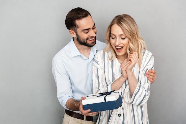 Primo piano fotografico di un uomo brunetta in abbigliamento casual che sorride e fa un regalo alla sua ragazza isolata su un muro grigio