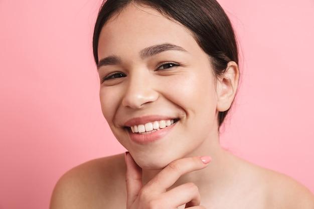 Primo piano fotografico di una gioiosa ragazza senza camicia con i capelli scuri che ride e guarda la parte anteriore isolata sul muro rosa