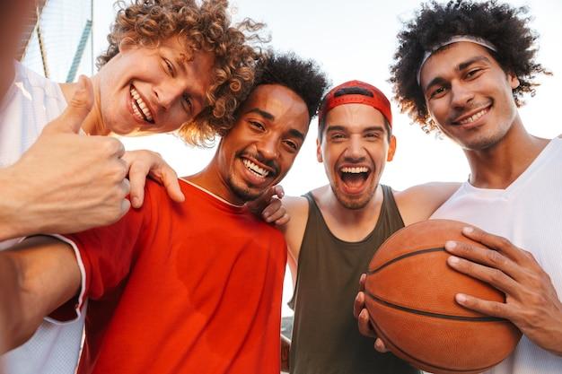 Primo piano della foto di uomini sportivi muscolosi che sorridono e che prendono selfie, mentre giocano a basket al parco giochi all'aperto durante la giornata di sole estivo