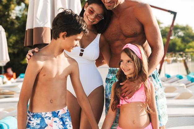 Primo piano della foto della famiglia caucasica sorridente con i bambini che riposano vicino alla piscina di lusso, con le sedie a sdraio e gli ombrelli bianchi di modo durante le vacanze