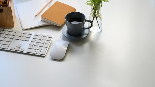 Foto della tazza di caffè, della tastiera, del topo, delle note, della matita e della pianta in vaso che uniscono sulla tavola bianca moderna. apparecchiature per ufficio piatte. concetto di lavoro confortevole.