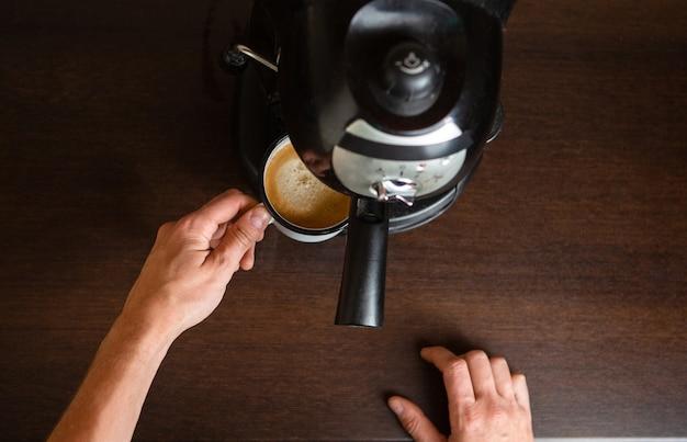 Foto della macchinetta del caffè, mani dell'uomo che versa il caffè nella tazza in cucina
