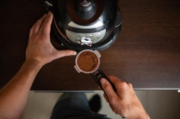 Foto della macchina per il caffè, mano dell'uomo che versa il caffè in cucina