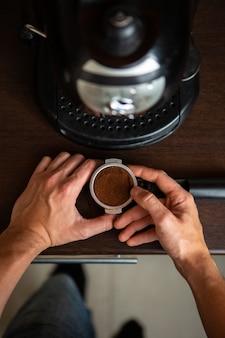 Foto della macchinetta del caffè, mano dell'uomo che versa il caffè in cucina