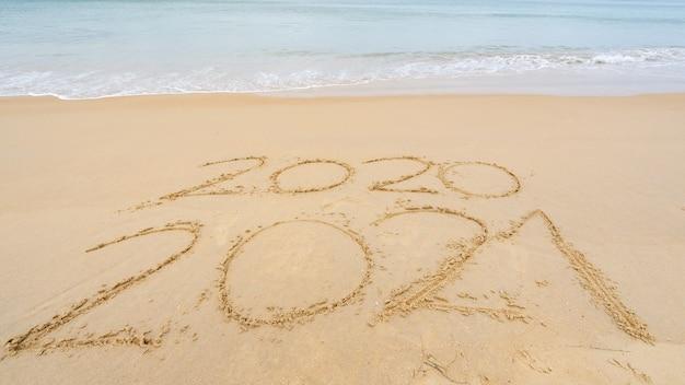 Foto del testo del nuovo anno 2021 in arrivo e del 2020 del testo dell'iscrizione sulla spiaggia con l'onda