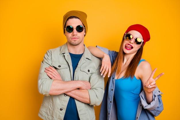 Foto di fiducioso ragazzo ragazza coppia mani incrociate leccare la lingua labbra godersi il fine settimana fare v-sign indossare camicia denim jeans giacca isolato su sfondo di colore brillante