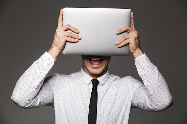 Foto di un uomo d'affari contenuto sorridente e in posa tenendo il computer portatile d'argento alla sua testa, isolato sopra il muro grigio