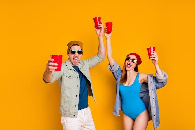 Foto di cool trend due persone ragazzo ragazza tenere bicchiere di plastica birra celebrare estate festa in spiaggia indossare costumi da bagno camicia denim jeans giacca isolato su sfondo di colore brillante brillante