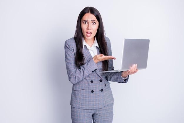 Foto di pazzo arrabbiato donna d'affari tenere notebook netbook cattiva connessione wifi internet dispiaciuto terribile costoso fornitore disconnettere abbigliamento formale abito scozzese isolato colore grigio sfondo