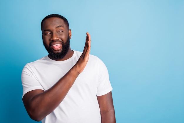 Foto di un pazzo ansioso con la bocca aperta mostra il segnale di stop guarda copyspace indossa una maglietta bianca su sfondo blu