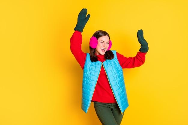 Foto di una ragazza pazza eccitata che si gode il ballo delle vacanze invernali alza le mani indossa un maglione pantaloni isolato su uno sfondo di colore brillante