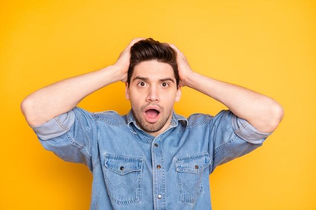 Foto di un pazzo pazzo che afferra la sua testa dopo aver saputo che è in bancarotta licenziato lontano dal lavoro bianco isolato muro di colori vivaci con emozioni negative spaventate sul viso