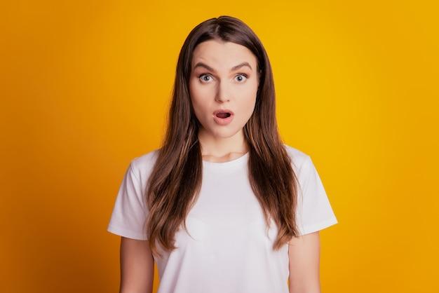 Foto di una pazza donna sorpresa con la bocca aperta che indossa una maglietta bianca su sfondo giallo