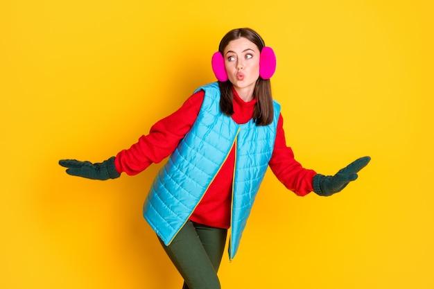 Foto di curiosa sorpresa divertente ragazza carina adolescente andare a piedi guarda copyspace vuole preparare un regalo di natale segreto indossare pantaloni maglione isolati su sfondo di colore brillante