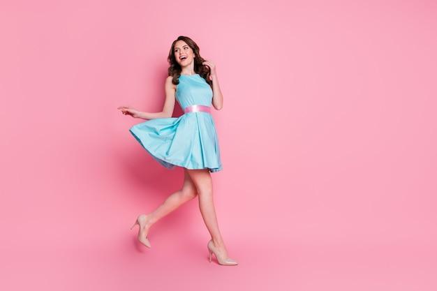 Foto di una signora riccia affascinante di buon umore che indossa un vestito blu verde acqua isolato sfondo di colore rosa