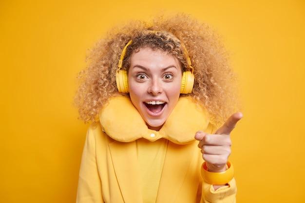 La foto di una donna dai capelli ricci con un'espressione felice e sorpresa tiene la bocca aperta indica direttamente alla telecamera