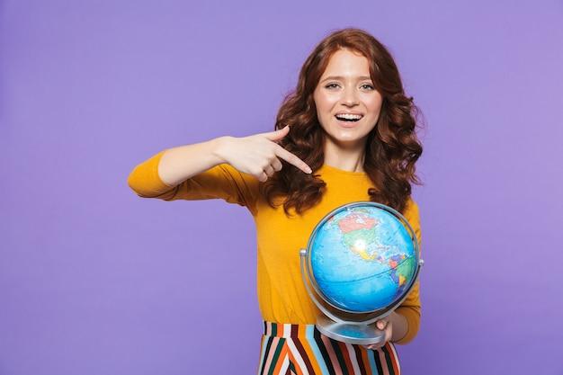Foto della donna riccia della testarossa che porta i vestiti gialli che sorridono e che tengono il globo della terra sopra la porpora