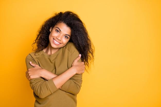 Foto di ricci ondulata allegra bella affascinante ragazza positiva che si abbraccia sorridente raggiante con amore di sé isolato su sfondo di colore vibrante