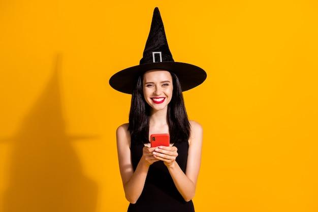 Foto di carino affascinante giovane mago signora tenere telefono raggiante lucido sorridente allegro dare feedback evento indossare nero mago copricapo vestito isolato colore giallo brillante sfondo