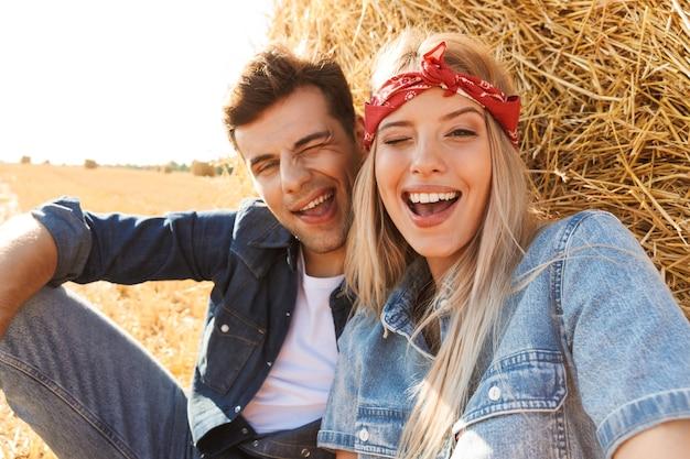 Foto di coppia carina uomo e donna sorridente mentre è seduto sotto un grande pagliaio in campo dorato, durante la giornata di sole