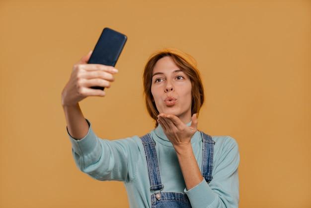 La foto della graziosa contadina scatta un selfie e fa un bacio d'aria. indossa tute e cappello in denim, sfondo di colore marrone isolato.