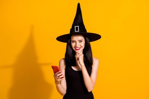 Foto di carino adorabile giovane mago signora mano mento tenere telefono raggiante sorridente post foto evento social network indossare nero mago copricapo vestito isolato colore giallo brillante sfondo