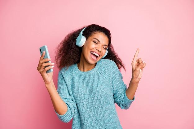 Foto di carino bella casual dolce casual elegante elegante donna alla moda che indossa un maglione blu ricci ondulati marrone haited con gli occhi chiusi tenendo il telefono ballando isolato color pastello parete