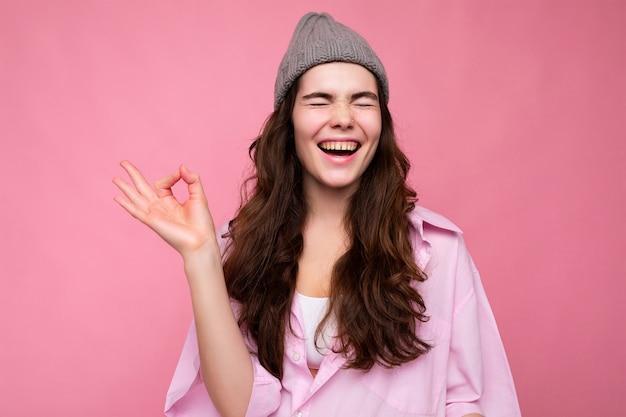 Foto di una bella donna adulta positiva e accattivante che indossa abiti casual isolati su una parete di fondo