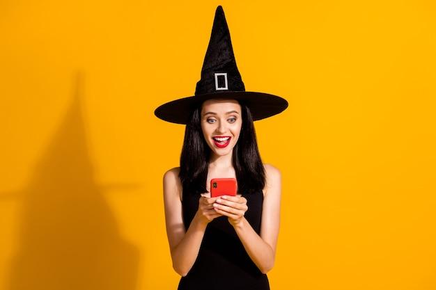 Foto di carina bella giovane mago signora tenere telefono eccitato sguardo bocca aperta amico invitare evento cosplay indossare nero mago copricapo vestito isolato sfondo di colore giallo brillante