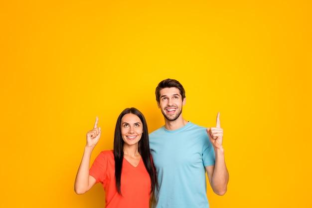 Foto di due persone sveglie coppia ragazzo e signora che abbracciano dirigendo le dita su spazio vuoto prezzi bassi shopping indossare casual blu arancione t-shirt jeans isolato giallo parete di colore