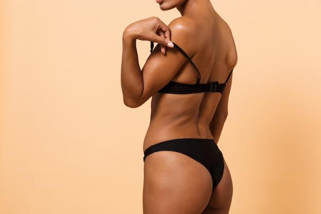 Foto di una donna dalla carnagione scura che indossa lingerie nera, in piedi isolato sul muro beige