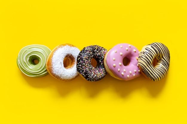 Foto di diverse ciambelle dolci su giallo