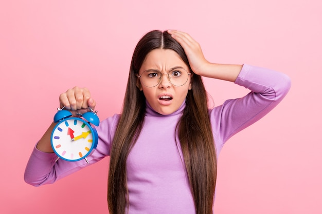 Foto di una ragazzina delusa e impressionata che tiene la testa dell'orologio che tocca la mano isolata su uno sfondo di colore pastello