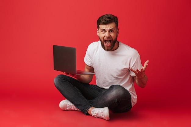 Foto di scontento annoiato uomo in t-shirt e jeans urlando e gesticolando con irritazione mentre è seduto sul pavimento con il laptop, isolato su sfondo rosso