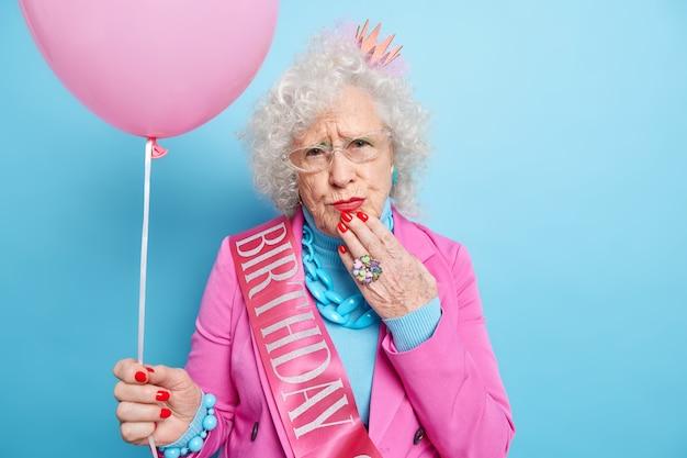 La foto della donna europea rugosa scontenta indossa il trucco e la manicure festeggia il compleanno