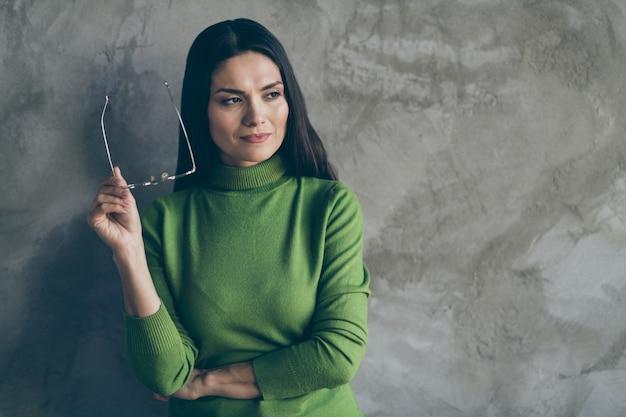 Foto della donna seria interessata sognante che si è tolta gli occhiali guardando nella pianificazione dello spazio vuoto scegliendo il fondo grigio isolato del muro di cemento