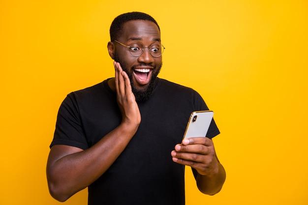 Foto di estatico uomo felicissimo che naviga attraverso il suo telefono che si rallegra nel ricevere notifiche positive in t-shirt isolato vivido colore giallo muro