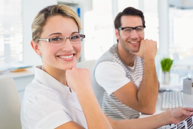 Redattori di foto che sorridono alla macchina fotografica con le mani sotto il mento
