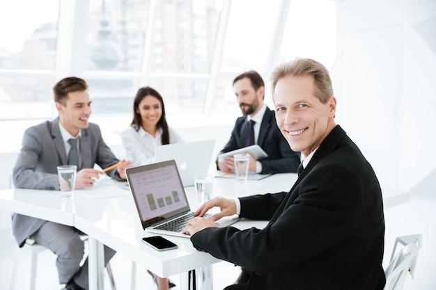 Foto di un uomo d'affari anziano in giacca e cravatta seduto al tavolo con un laptop in ufficio con i colleghi