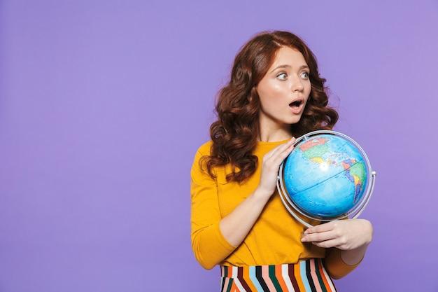 Foto della donna emotiva rossa che indossa abiti gialli sorridendo e tenendo il globo terrestre sopra viola