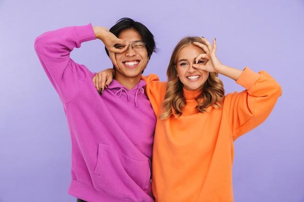 Foto di studenti emotivi di giovani coppie amici in piedi isolato, mostrando il gesto giusto.