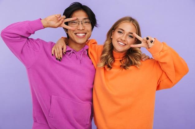 Foto di studenti emotivi di giovani coppie amici in piedi isolato, mostrando gesto di pace