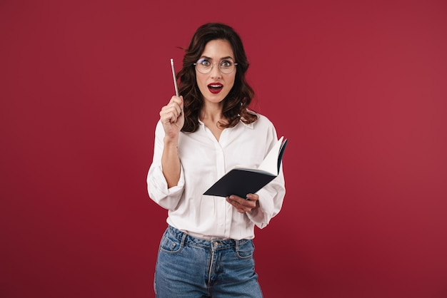 La foto di una giovane donna emotiva con gli occhiali isolati sul muro rosso che scrive note sul taccuino ha un'idea.