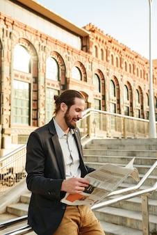 Foto di un uomo barbuto europeo degli anni '30 in abito classico, che cammina per una strada cittadina e legge il giornale sull'economia sulle scale della città